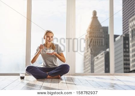 Corn cereals is my favorite breakfast. Joyful young woman is sitting near window with relaxation. She is looking at camera and smiling