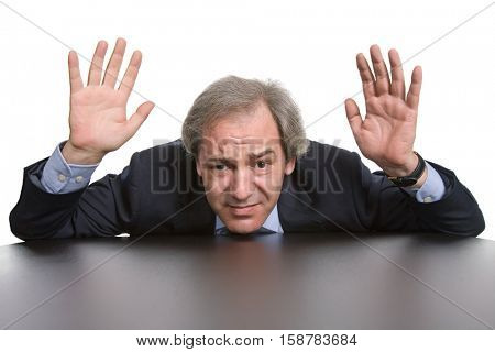 scared mature businessman on a desk, isolated on white