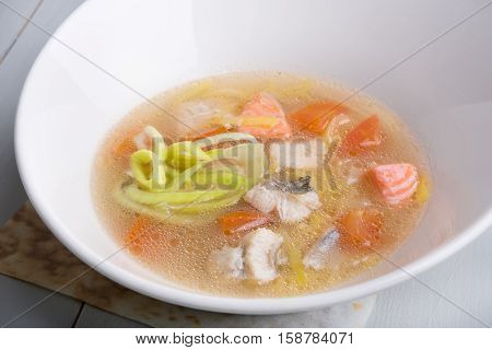 Fish soup in a white bowl on the table