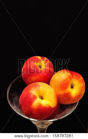 A glass filled with nectarines isolated on a black background