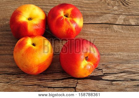 Four Nectarines isolated on a wooden background