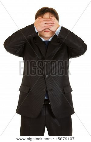 Modern businessman making see no evil gesture isolated on white