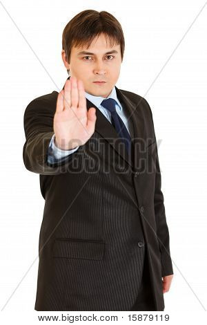 Confident modern businessman showing stop gesture isolated on white