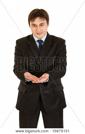 Friendly businessman presenting something on empty hands isolated on white