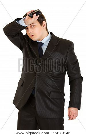Tired businessman holding his hand with mobile near forehead isolated on white