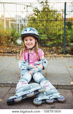 Smiling preschooler with inline roller skates on sitting outside