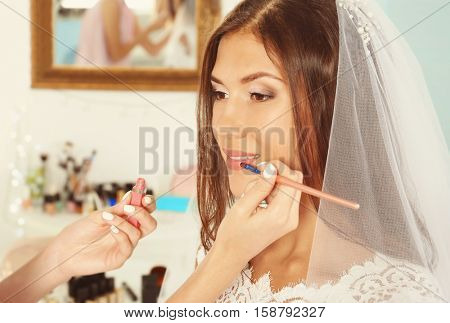Wedding preparation. Professional makeup artist applying lip gloss on bride's lips