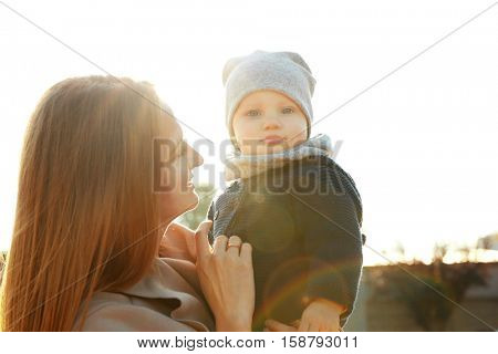 Young woman with cute little baby outdoors