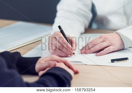 Female doctor taking notes during patient's medical exam writing medical history record for the woman
