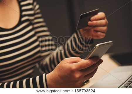 M-commerce and m-banking concept with smartphone and credit card in female hands