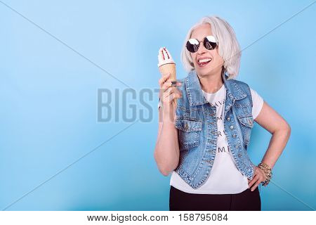 Feel young. Senior expressive beautiful woman showing tongue and holding icecream while standing against isolated blue background.