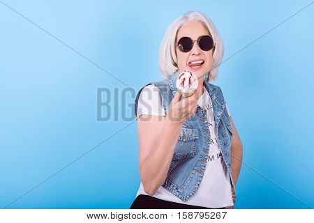 Feel young again. Senior charming happy woman holding icecream and showing tongue while standing against isolated blue background.