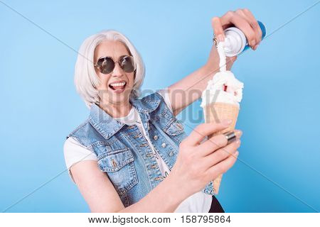 I like icecream. Delighted senior pretty woman smiling and adding cream in icecream while standing against isolated blue background.