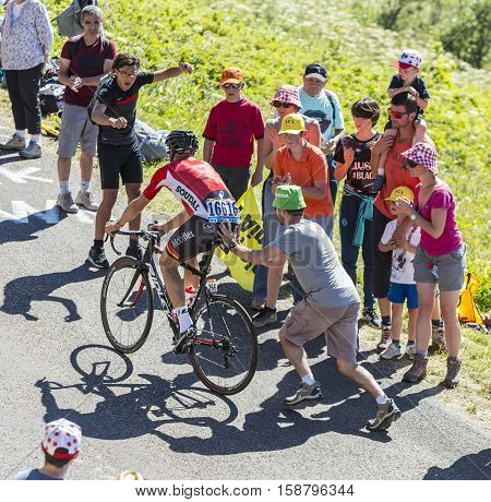 Col du Grand ColombierFrance - July 17 2016: Unidentified spectator is pushing the cyclist Adam Hansen of Team Lotto-Soudal while climbing the road to Col du Grand Colombier in Jura Mountains during the stage 15 of Tour de France 2016.