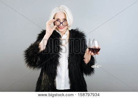 I like wine. Happy senior pleasant woman holding wineglass and smiling while standing against isolated gray background.