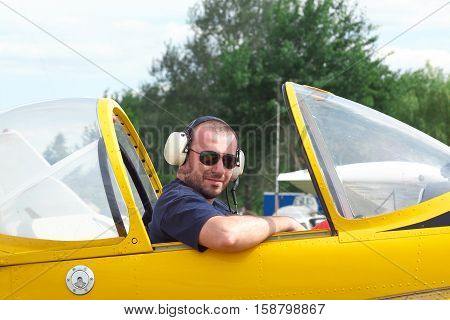 Pilot sitting in the cockpit of a light aerobatic plane with the canopy open