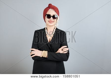 Ready to have party. Stylish pretty senior woman smiling and crossing hands on her chest while standing against isolated gray background.