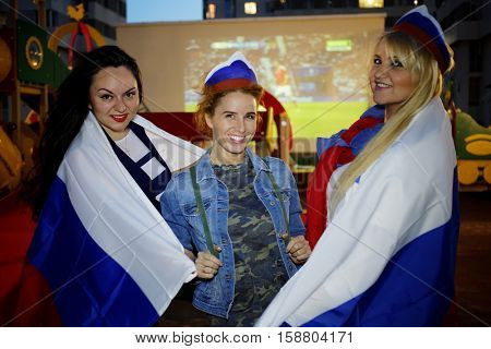 Three women covered with flags of Russia pose against screen with soccer game outdoor at playground.