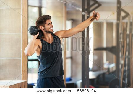 Fitness man makes selfie in gym with weight