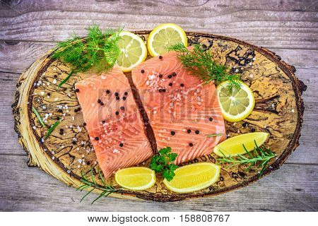 Overhead shot on fresh Salmon steak on wooden birch stump pickled lemon pepper sea salt rosemary parsley dill
