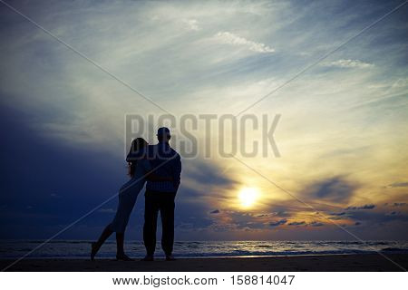 Wide low angle shot warmth embracing of happy romantic couple in love on the beach at sunset. People in love. Spending time together. Romantic atmosphere