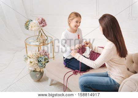 Appreciate the moment. Happy nice young mother looking at her daughter and teaching her to knit while spending time with her