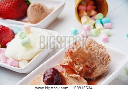 Ice cream sundae, strawberry and candies on a white table