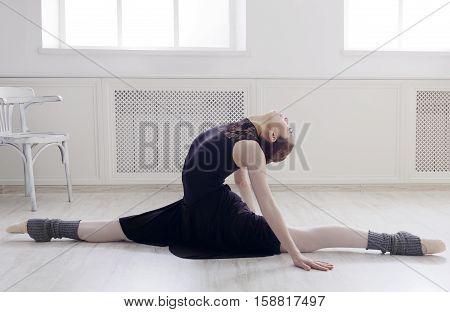 Classical Ballet dancer portrait. Beautiful graceful ballerine in black practice split ballet position in class room background. Ballet class training, high-key soft toning.
