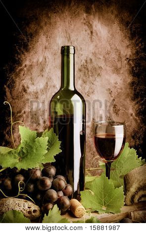 Red wine still life in old style with grunge wall background