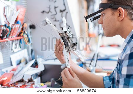 Problems to solve. Delighted young handsome man discovering drone detail while sitting in workroom and working as a repairman.
