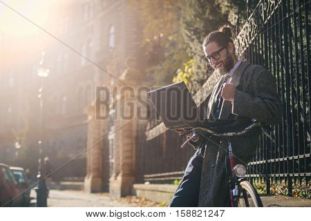 Student checking his laptop outside