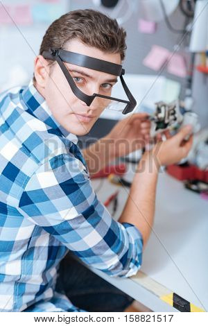 Responsibility in work. Portrait of a young handsome man repairing drone camera mechanism while discovering chips and working as a repairman.