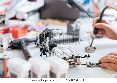 Creating device. Close up of young mans hands soldering drone mechanism while using soldering iron and working as a repairman.