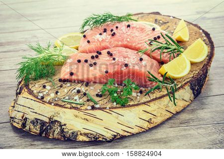 Shot of fresh Salmon steak on wooden birch stump pickled lemon pepper sea salt rosemary parsley dill
