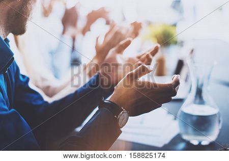 Close up view of young business partners applauding to reporter after listening report at seminar. Professional education, work meeting, presentation or coaching concept.Horizontal, blurred background