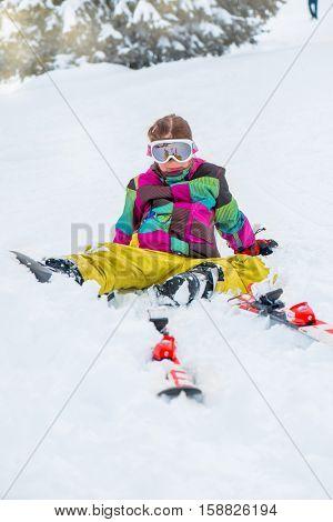 Happy kid in ski goggles sitting in snow