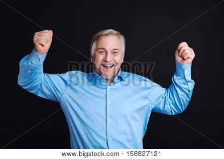 Feeling happiness. Grey-haired man expressing positivity holding both hands in air while standing against black background