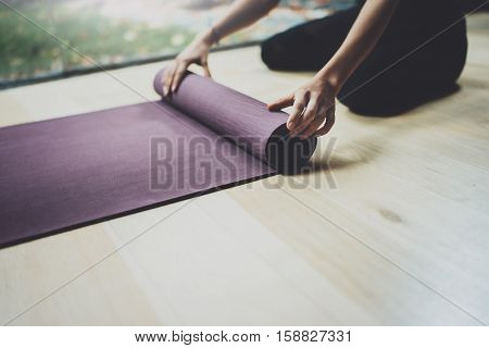 Close up view of female hands.Gorgeous young woman practicing yoga indoor. Beautiful girl preparing mats for practice class.Calmness and relax, happiness concept.Horizontal, blurred background