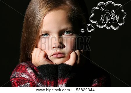 Sad little girl dreaming of happy family, black background. Adoption, custody and childcare concept.
