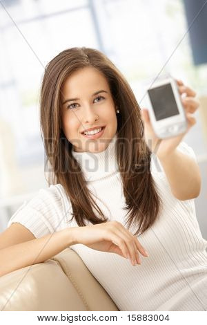 Smiling woman showing mobile phone, holding up to camera, smiling.?