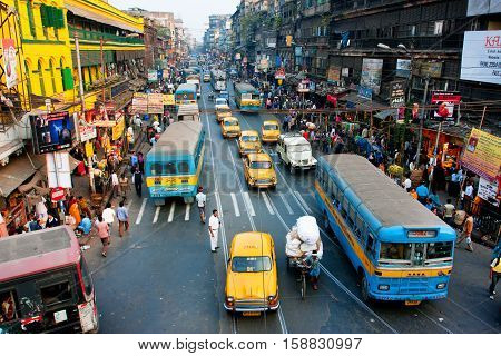 KOLKATA, INDIA - JAN 20, 2013: Lines of the yellow Ambassador taxi cabs and buses on the road of the city on January 20, 2013 in Calcutta, India. Kolkata has a density of 814.80 vehicles per km road length