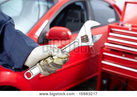 Hands with wrench. Mechanic. Auto repair shop.