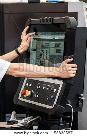 Operator hands on lcd screen of CNC machine