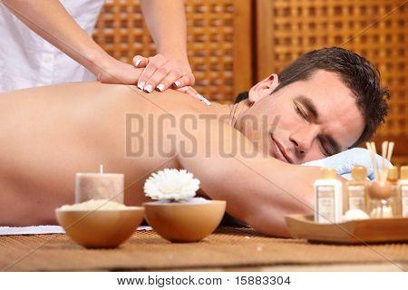 joven guapo recibir un masaje. Spa
