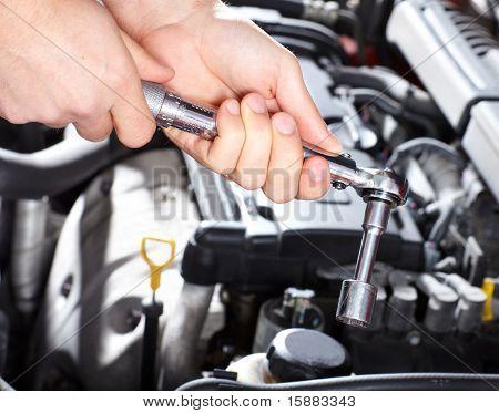Mão com a chave. Mecânico. Oficina de reparação automóvel.