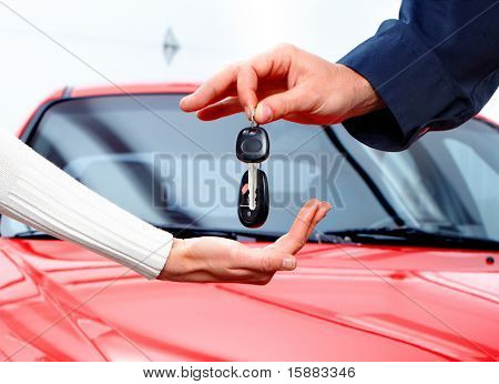 Man handing woman automobile keys. New Car