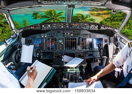 Airplane cockpit flying on Kee Beach, Kauai, Hawaii, United States, with pilots arms and blank white papers for copy space.
