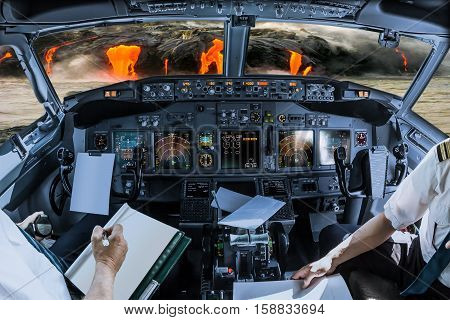 Airplane cockpit flying on Kilauea Volcano, Big Island, Hawaii, United States by sunset, with pilots arms and blank white papers for copy space.