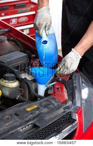 Lavaparabrisas. Mecánico trabajando en el taller de reparación de automóviles.