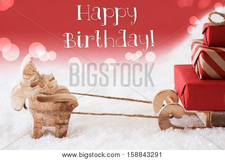 Moose Is Drawing A Sled With Red Gifts Or Presents In Snow. Christmas Card For Seasons Greetings. Red Christmassy Background With Bokeh Effect. English Text Happy Birthday